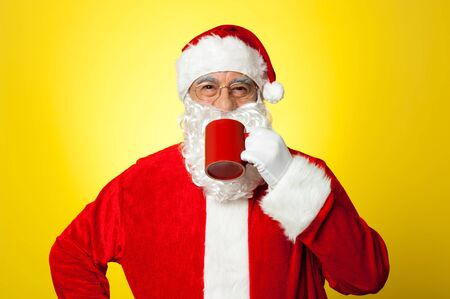 Relaxed Santa enjoying his cup of coffee. Isolated against yellow background. Stock Photo - 16510646