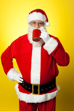 Portrait of a aged Santa sipping coffee. Hand on his waist. Stock Photo - 16510989