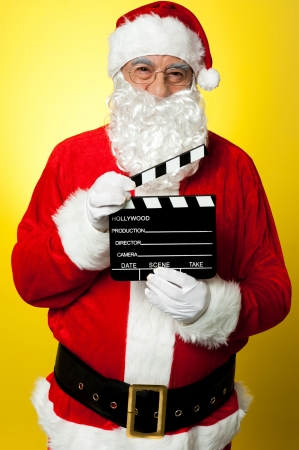kris kringle: Its time for next shot. Cheerful Kris Kringle posing with clapperboard. Stock Photo