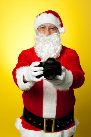 Santa Claus holding up his brand new DSLR. Smile please Stock Photo - 16510762