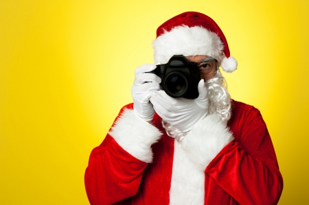 Say cheese! Santa capturing a perfect moment. Isolated over yellow background. Stock Photo - 16510654