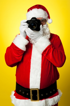 smile please: Smile please! Santa capturing a perfect frame. All on yellow background. Stock Photo