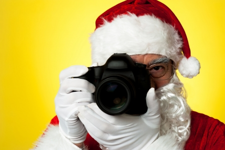 Aged Santa adjusting camera lens before click. Isolated against yellow Stock Photo - 16510775