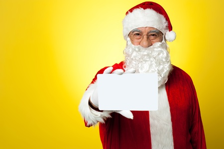Santa holding blank white placard in his outstretched arm. Stock Photo - 16510467