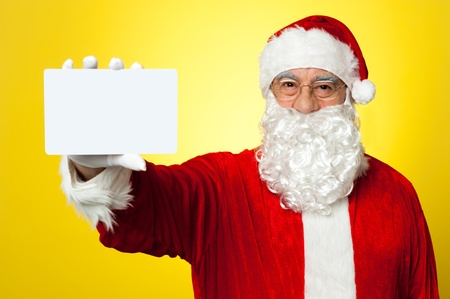 Saint Nick flashing a blank placard to the camera. Advertise your business here. Stock Photo - 16510653