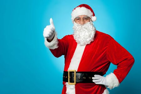 Father Santa gesturing thumbs up isolated against blue background. Stock Photo - 16510628