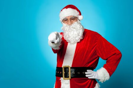 Handsome man in Santa costume pointing at you isolated over blue background.