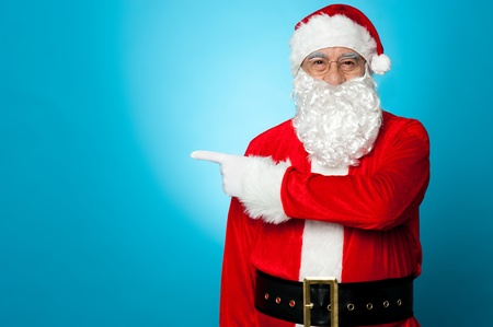 Saint Nicholas facing the camera and pointing sideways, copy space concept. Stock Photo - 16510507