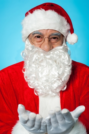 Smiling aged Santa posing with open palms. Indoor studio shot with blue background. Stock Photo - 16511175