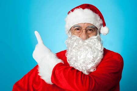 Father Christmas on blue background pointing away. Copy space concept. Stock Photo - 16510760