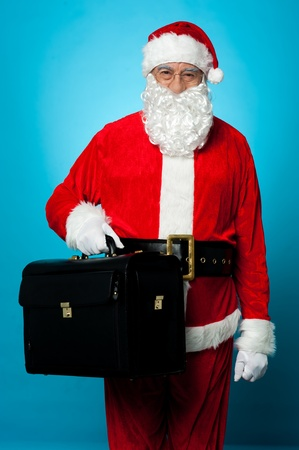 nick: Santa is all set to visit his new office, holding briefcase. Casual shot over blue background.