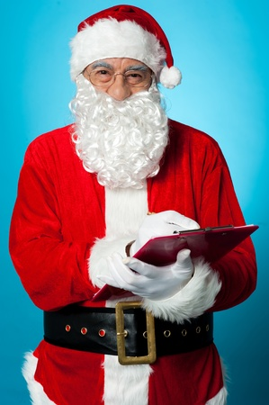 Father Nicholas preparing a list of gift recipients on clipboard. Isolated over blue. Stock Photo - 16511162
