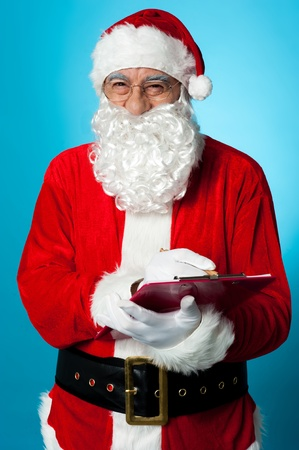 Santa Claus making his list of the good children. Is your name in it? Stock Photo - 16511114