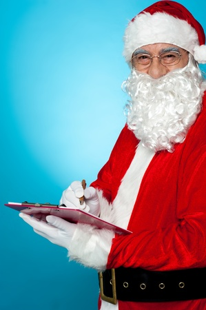 Santa Claus making notes in the wish list and smiling at camera. Stock Photo - 16510951