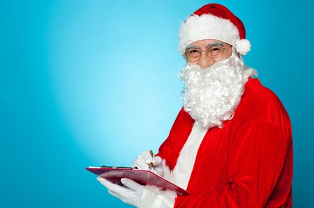 A thoroughly modern Santa claus checks his list on clipboard. Isolated over blue background. Stock Photo - 16510659