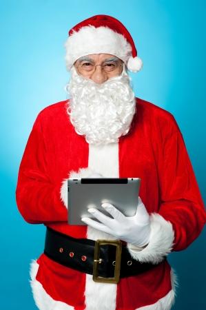 Modern Santa using digital touch screen device. Facing camera and smiling. photo