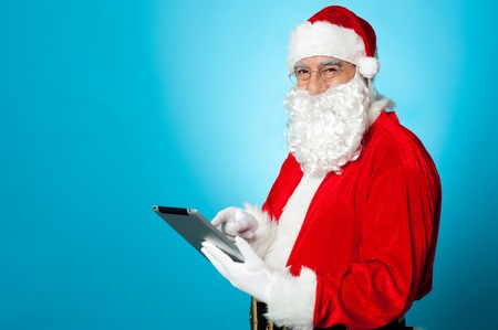 Santa using newly launched electronic tablet device. Studio shot photo