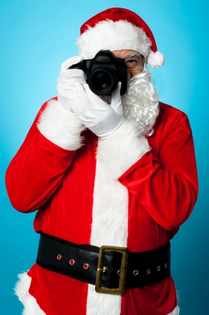 Smile Please! Santa Claus turns into a pro photographer. Stock Photo - 16511116