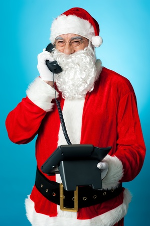 Modern Santa passing greetings over a phone call isolated against blue background. Stock Photo - 16511066
