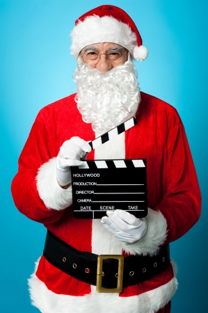 christmas movies: Bespectacled Santa holding a clapperboard. Get ready for next shot.