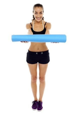 Attractive woman in gym attire  holding a blue mat in her outstretched arms photo