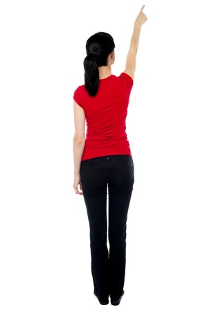 Back pose of woman in casuals pointing away isolated against white. photo