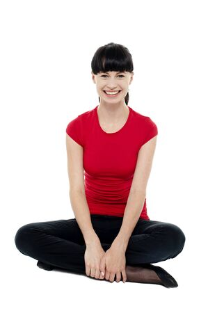 Relaxed smiling trendy woman sitting in studio floor. Legs crossed and facing camera. photo