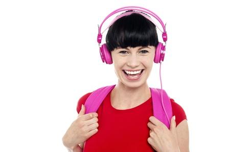 chirpy: Chirpy young girl having fun, listening to music using pink headphones.