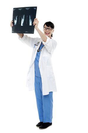 Nurse holding x-ray sheet against light to examine the same. Full length shot. Stock Photo - 16511274