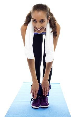 bending down: Flexible mujer agach�ndose hasta los dedos del pie aislado sobre fondo blanco. Foto de archivo
