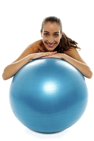 Woman leaning over big blue swiss ball and smiling at camera. photo