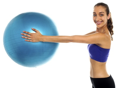 Side view of a fitness enthusiast holding a swiss ball. Casual shot photo