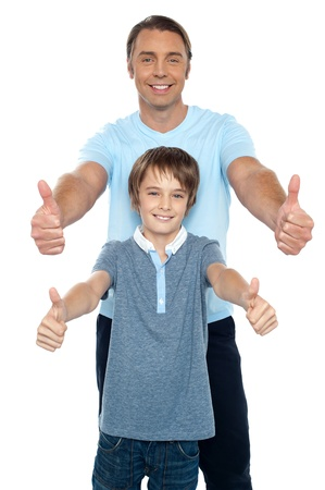 capture the moment: Handsome father and son showing thumbs up gesture to the camera. Capture the moment.