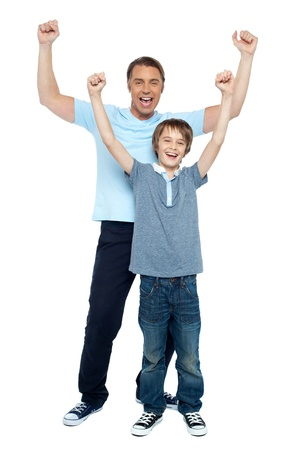 arms raised: Father and son celebrating their success. Rejoicing with raised arms.
