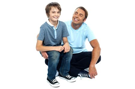 Affectionate father admiring his sweet son on his lap. Sitting on the floor, legs crossed. Stock Photo - 16634511