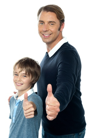 yup: Confident father and son duo  gesturing thumbs up sign. Smiling faces Stock Photo