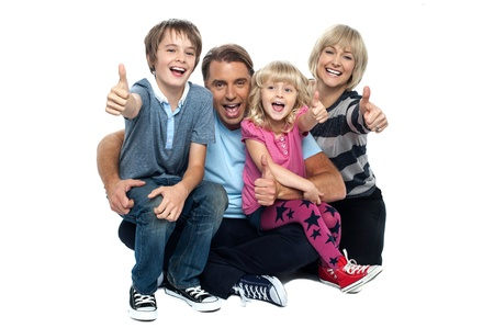 thumbs up: Happy thumbs up family of four sitting on studio floor. Stock Photo