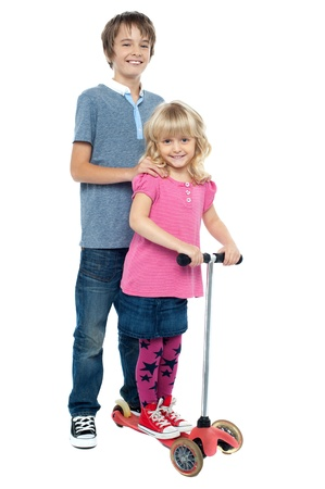 Brother holding her sister as she rides her toy scooter. Casual studio shot. photo