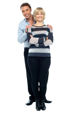 pareja abrazada: Marido de mediana edad sosteniendo su esposa por detr�s. Esposa posando con elegancia con los brazos cruzados. Foto de archivo