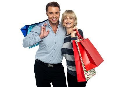 夫と妻の買い物を楽しんでします。カラフルな買い物袋を運ぶ。
