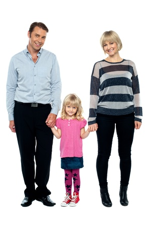tightly: Cute daughter holding hands of her parents tightly. Full length studio shot. Stock Photo