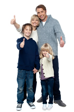 four person: Adorable family in winter clothes gesturing thumbs up. Full length portrait over white background.