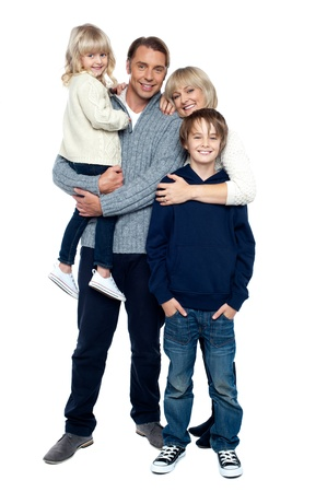 Affectionate family of four posing in winter outfits. Full length studio shot.