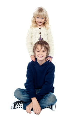 Smart young boy sitting with his legs crossed and his sister standing behind him. photo
