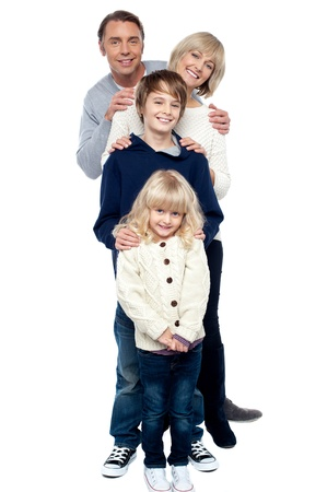 Affectionate family of four standing in a row. Hands on each others shoulders. Stock Photo - 16634471