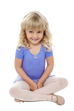 Adorable kid sitting with crossed legs on the floor. Cutely smiling at the camera.