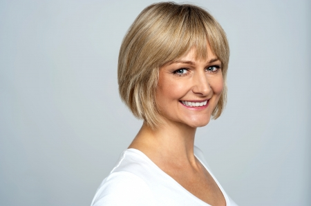 middle aged woman: Snap shot of a cheerful blonde, side pose. Gray background. Stock Photo