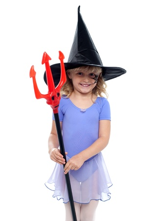 masquerading: Cute girl holding pitchfork and wearing witches hat. Halloween concept