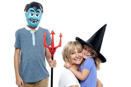 masquerading: Mother hugging her daughter in witches hat while son wearing dracula face mask and holding pitchfork. Stock Photo