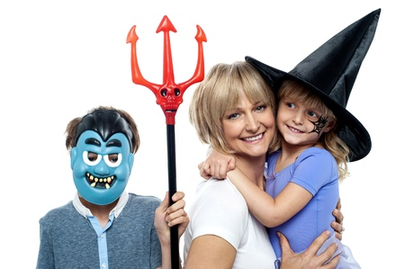 masquerading: Mom with son and daughter. Halloween dress up. All against white background.